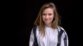 Porträt des jungen kaukasischen langhaarigen Mädchens im karierten Hemd herzlichst lächelnd in Kamera auf schwarzem Hintergrund lizenzfreie stockfotografie