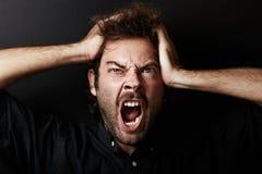 Porträt des jungen Kerls, der seinen Kopf in den Händen ergreift Lizenzfreie Stockfotografie