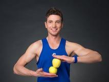 Porträt des jungen lächelnden Bodybuilders, der Apfel hält Lizenzfreies Stockbild