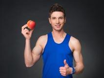 Porträt des jungen lächelnden Bodybuilders, der Apfel hält Stockfoto