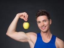 Porträt des jungen lächelnden Bodybuilders, der Apfel hält Stockfotos