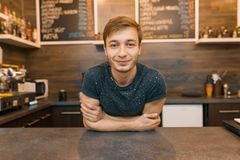 Porträt des jungen lächelnden männlichen barista mit den Armen kreuzte die Stellung hinter Cafézähler Kaffeestubegeschäftskonzept lizenzfreie stockfotografie