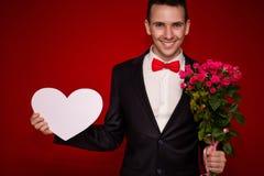 Porträt des jungen lachenden Geschäftsmannes mit Blumen und großem Papierherzen Lizenzfreie Stockfotografie