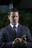 Porträt des jungen lateinischen Geschäftsmannes Using Cell Phone Stockfotos