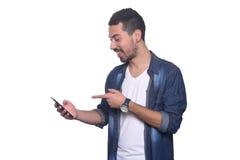 Porträt des jungen lateinischen Mannes, der auf seinen Smartphone zeigt Stockfotos