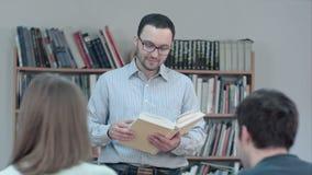 Porträt des jungen Lehrerlesebuches im Klassenzimmer stock video