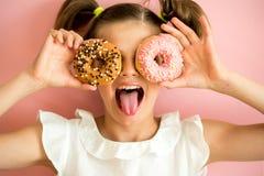 Porträt des jungen Mädchens schauend durch zwei rosa Schaumgummiringe, rosa Hintergrund, Lizenzfreie Stockbilder