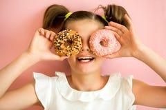 Porträt des jungen Mädchens schauend durch zwei rosa Schaumgummiringe, rosa Hintergrund, Stockfotos