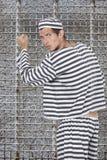 Porträt des jungen männlichen Gefangenen in der Uniform, die gegen Gefängniszelle steht Lizenzfreies Stockfoto