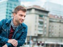 Porträt des jungen Mannes aufwerfend auf der Straße, Profil des hübschen Kerls Stockfotos