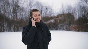 Porträt des jungen Mannes des Brunette in der schwarzen Haube, die telefonisch im Park des verschneiten Winters spricht Langsame  stock video footage