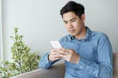 Porträt des jungen Mannes das blaue Hemd tragend, das mit Smartphone schaut und an seinem Sofa im Büro sitzt stockfotografie