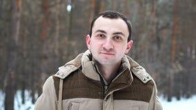 Porträt des jungen Mannes das, der an der Kamera im Winterwald blinzelt stock footage