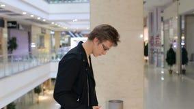Porträt des jungen Mannes in den Gläsern und in der Lederjacke in einem großen Einkaufszentrum stock footage