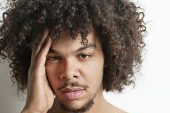 Porträt des jungen Mannes, der Kopfschmerzen über weißem Hintergrund hat Stockbild