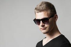 Porträt des jungen Mannes in der Sonnenbrille auf Grau Lizenzfreies Stockfoto