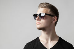 Porträt des jungen Mannes in der Sonnenbrille lokalisiert auf Grau Lizenzfreies Stockbild