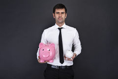 Porträt des jungen Mannes ein Sparschwein zwei halten Lizenzfreies Stockfoto