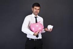 Porträt des jungen Mannes ein Sparschwein zwei halten Stockbild