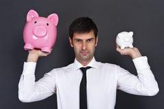Porträt des jungen Mannes ein Sparschwein zwei halten Lizenzfreie Stockfotografie