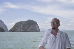Porträt des jungen Mannes gegen blaues Meer und Insel lizenzfreies stockbild