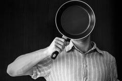 Porträt des jungen Mannes hinter schwarzer Bratpfanne Lizenzfreies Stockfoto