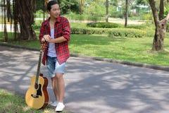 Porträt des jungen Mannes des Hippies, der Akustikgitarre am Park draußen halten sich entspannt Stockfotografie