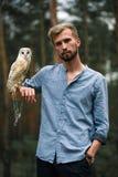 Porträt des jungen Mannes im Wald mit Eule in der Hand Lizenzfreie Stockfotografie
