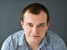 Porträt des jungen Mannes lokalisiert auf grauem Hintergrund Stockbilder