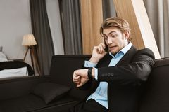 Porträt des jungen Mannes mit dem blonden Haar und des Bartes im schwarzen Anzug, der Uhr zur Hand mit dem erschrockenen Ausdruck Lizenzfreies Stockfoto