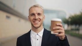 Porträt des jungen Mannes mit dem Kaffee, der die Kamera untersucht Lachendes nettes Porträt des erfolgreichen Geschäftsmannes stock footage