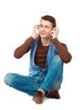 Porträt des jungen Mannes mit den Kopfhörern, die auf dem Boden sitzen Lizenzfreie Stockfotografie