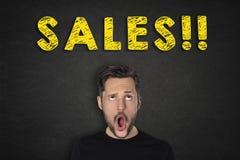 Porträt des jungen Mannes mit einem wow Ausdruck und 'Verkäufen!!! 'Text lizenzfreie stockfotografie