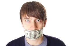 Porträt des jungen Mannes mit einer 100-Dollar-Banknote auf seinem Mund ist Stockfoto