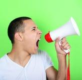 Porträt des jungen Mannes schreiend mit einem Megaphon gegen grünes Ba Lizenzfreie Stockfotografie