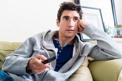 Porträt des jungen Mannes sitzend auf dem Sofa beim Fernsehen an h Lizenzfreie Stockbilder