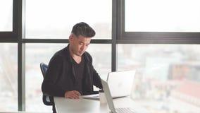Porträt des jungen Mannes sitzend an seinem Schreibtisch im Büro stock video