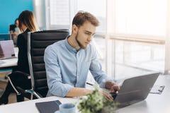 Porträt des jungen Mannes sitzend an seinem Schreibtisch im Büro lizenzfreie stockbilder