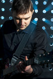 Porträt des jungen Mannes spielend auf Gitarre auf Stadium Lizenzfreies Stockfoto