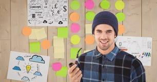 Porträt des jungen Mannes Tabakpfeife gegen klebrige Anmerkungen und Zeichnungen auf Wand halten Stockfotos