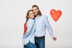 Porträt des jungen Mannes und der Frau, die ein Herz hält, formte Ballon und Papier Lizenzfreie Stockbilder