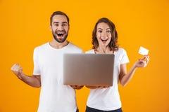 Porträt des jungen Mannes und der Frau, die silbernen Laptop und Kreditkarte, bei der Stellung lokalisiert über gelbem Hintergrun stockbild