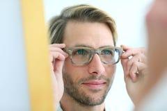 Porträt des jungen Mannes versuchend auf Brillen Lizenzfreie Stockbilder