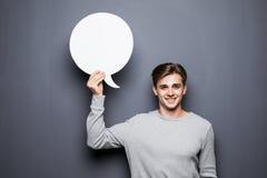 Porträt des jungen Mannes weiße leere Spracheblase mit Raum für den Text halten lokalisiert auf grauem Hintergrund Lizenzfreie Stockbilder