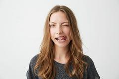 Porträt des jungen positiven hübschen Mädchens, welches die Kamera blinzelt betrachtet, Zunge über weißem Hintergrund zeigend Lizenzfreies Stockfoto
