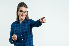 Porträt des jungen positiven Mädchens im lächelnden Blinzeln der Gläser, Kamera betrachtend Finger in der Seite über weißem Hinte Lizenzfreies Stockbild