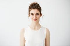 Porträt des jungen schönen Brunettemädchens, das Kamera über weißem Hintergrund betrachtend lächelt Lizenzfreies Stockfoto