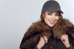 Porträt des jungen schönen lächelnden Modells, das modische Textiljacke mit Fuchspelz und modischer grauer Höchstkappe mit Schnür stockbild