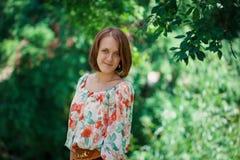 Porträt des jungen schönen Mädchens auf einem grünen Hintergrund Stockfotografie