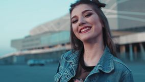 Porträt des jungen schönen Mädchens, das in Richtung zur Kamera lächelt Junge stilvolle Jeansabnutzung Frohe Stimmung, Glück akti stock video footage